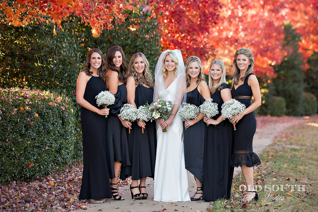 Orange fall leaves as the backdrop for the bridal party