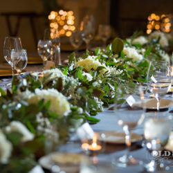 Head table with gold chargers and greenery runner