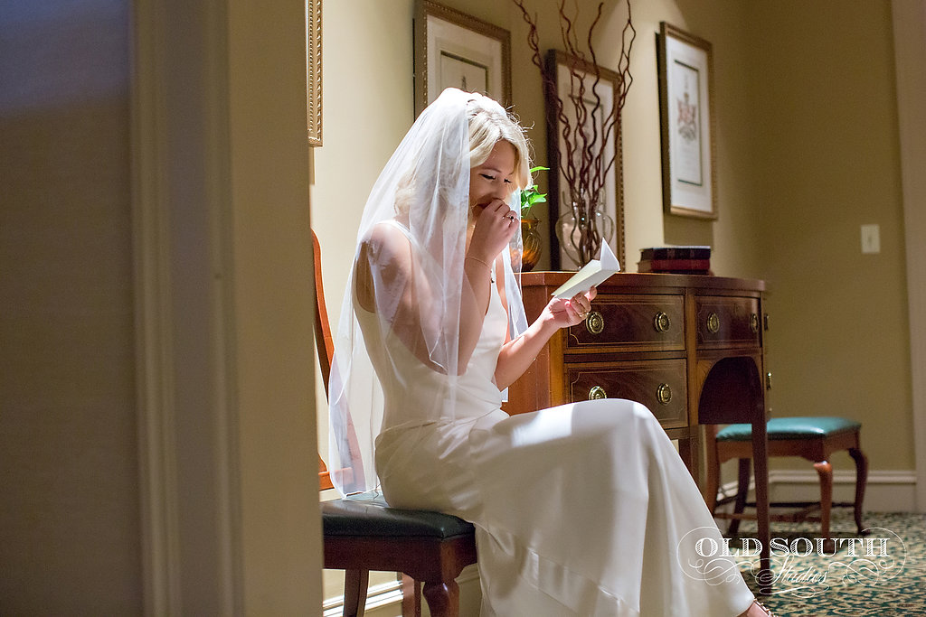 Bride reading a note from her groom on their wedding day