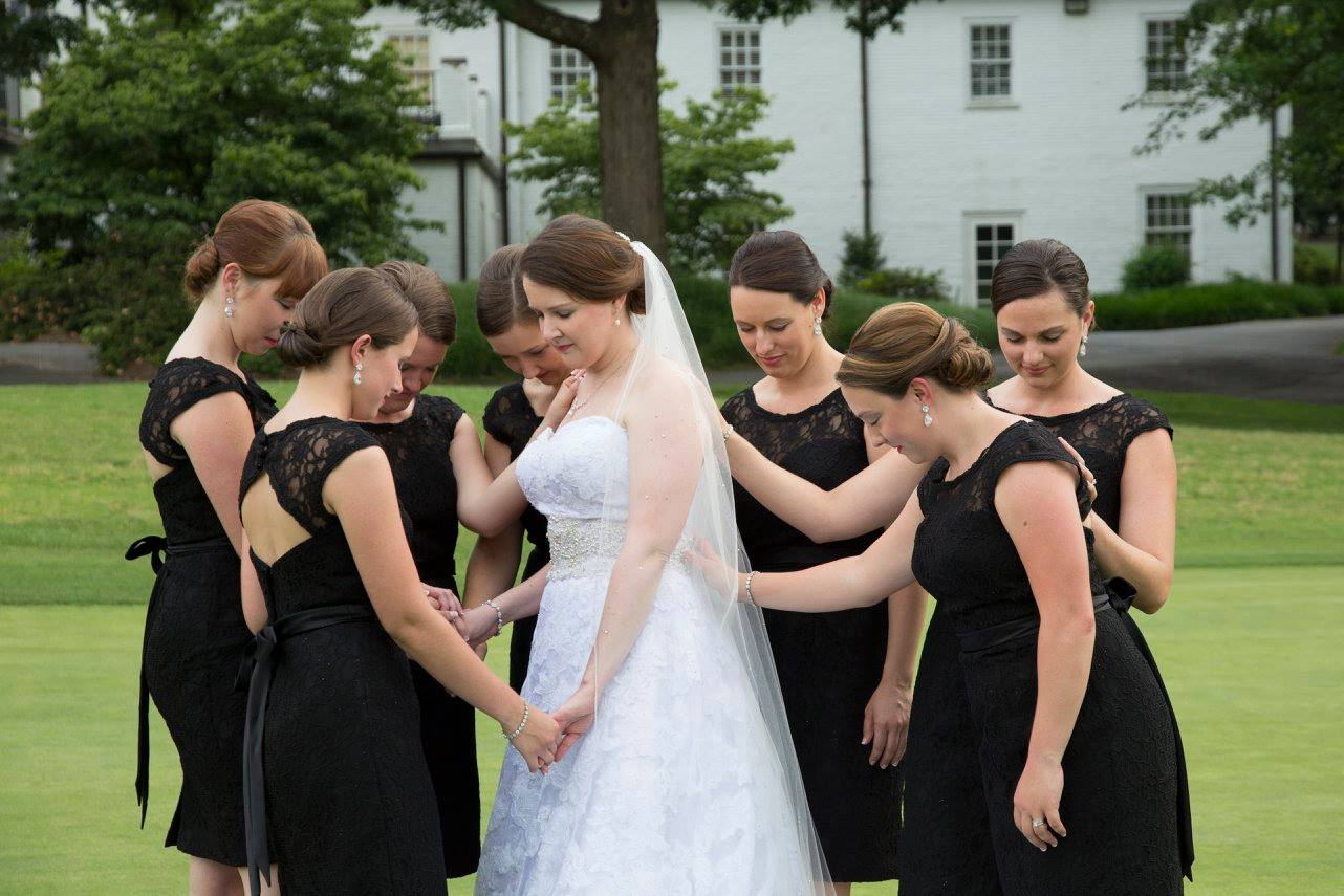 bridesmaids praying over the bride