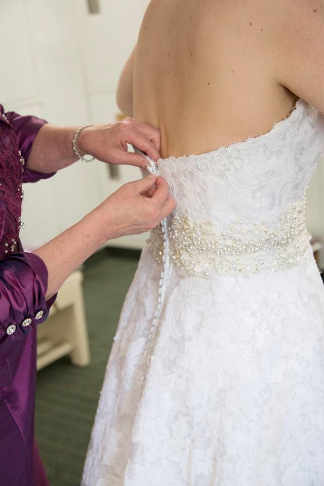 mom zipping up bride's dress