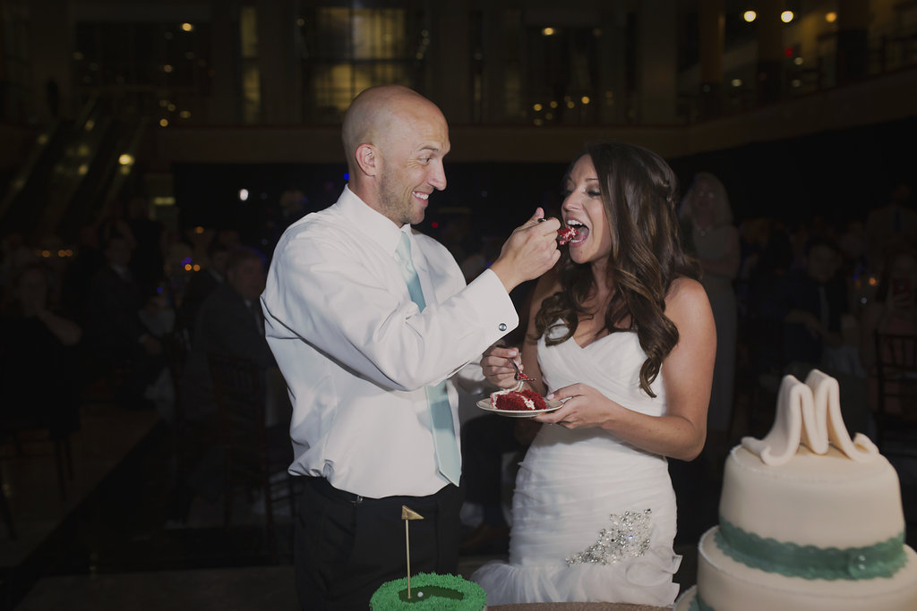 groom feeding bride cake after cutting the cake at Founders Hall Charlotte