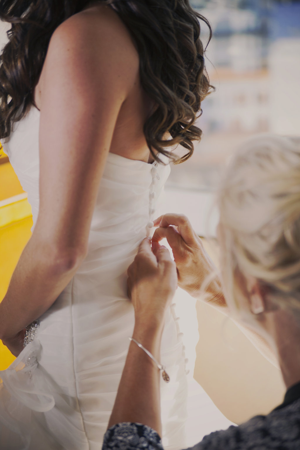 bride getting ready in her wedding gown