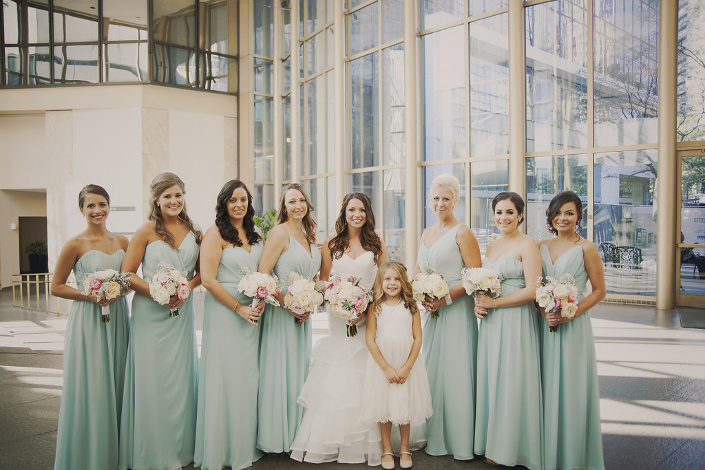 Bridesmaids in teal dresses with bride and bouquets