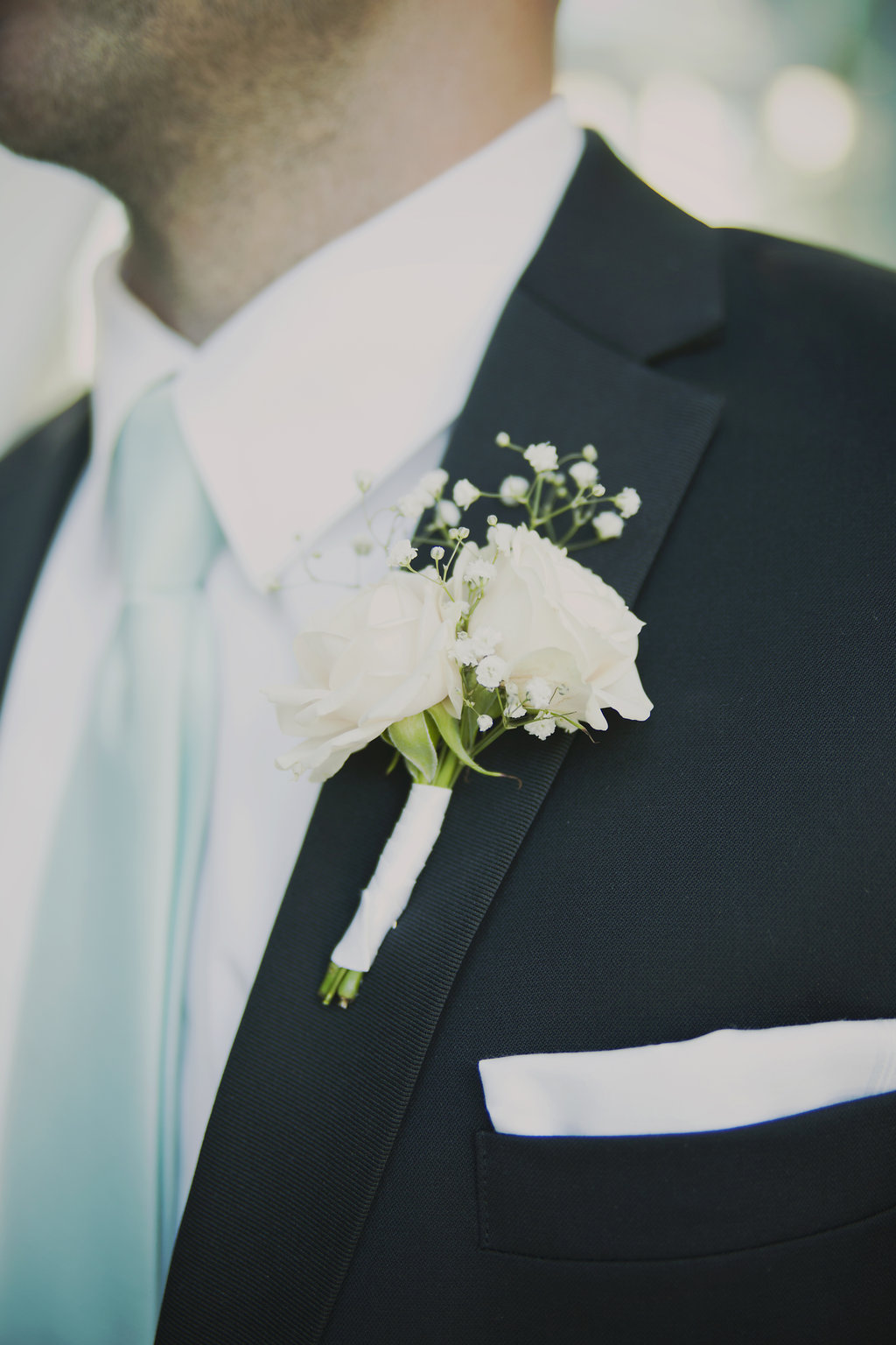 grooms boutonniere with roses and baby's breath