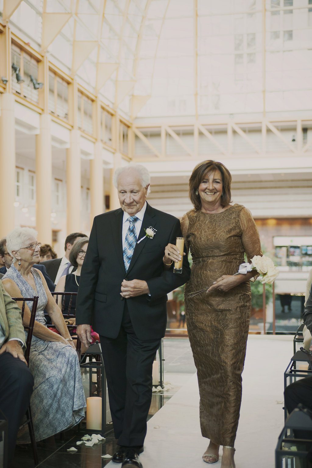 Proud mother of the bride being escorted down the aisle by the bride's grandfather.