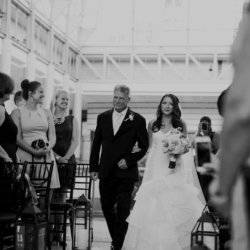 black and white photo of bride and father walking down the aisle