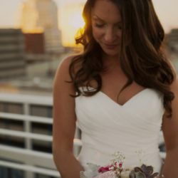Sunset photo of a bride in Uptown Charlotte in a New York Bride and Groom dress.