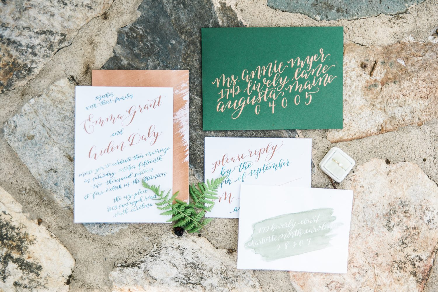 Green wedding invitation envelope with copper calligraphy.
