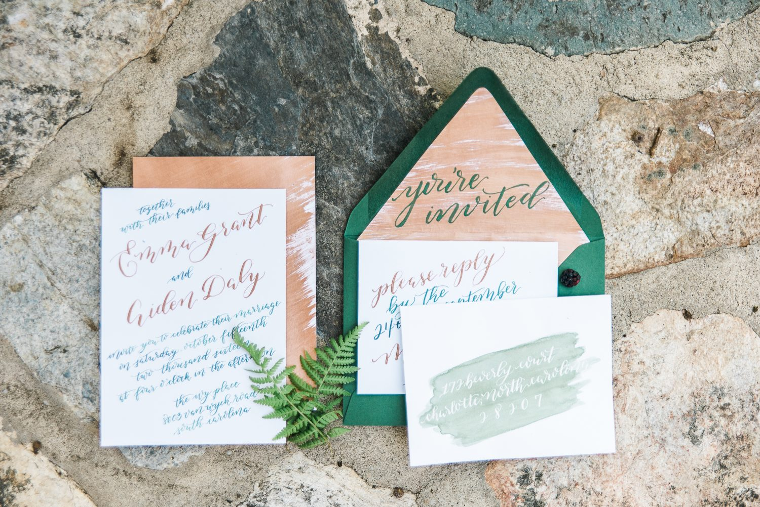 Green wedding envelope with copper inserts and custom calligraphy invitation.