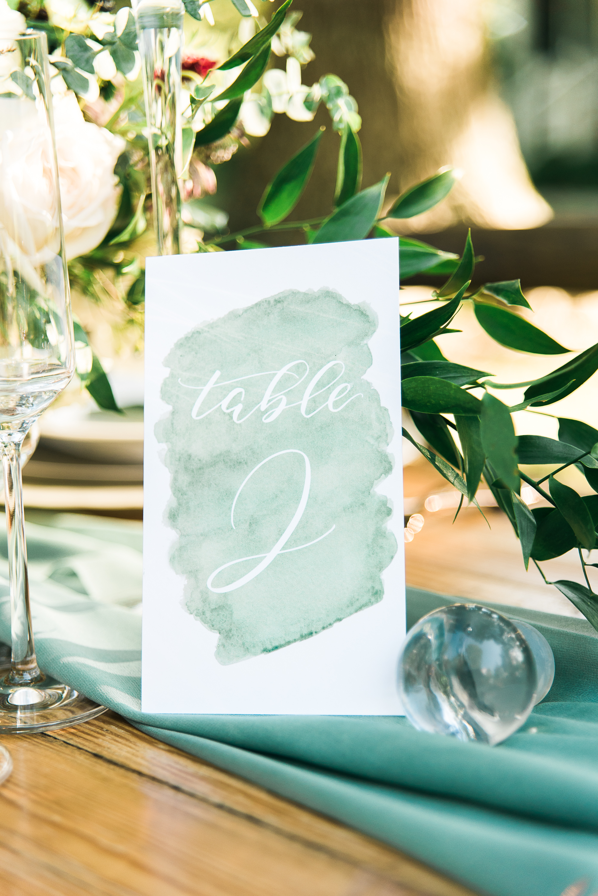 Light green table number in calligraphy and watercolor.