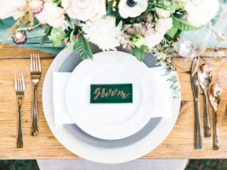 Place setting with a farm table, rose gold flatware, white charger, gray plate, white plate, white linen napkin, and a green tile calligraphy place card.