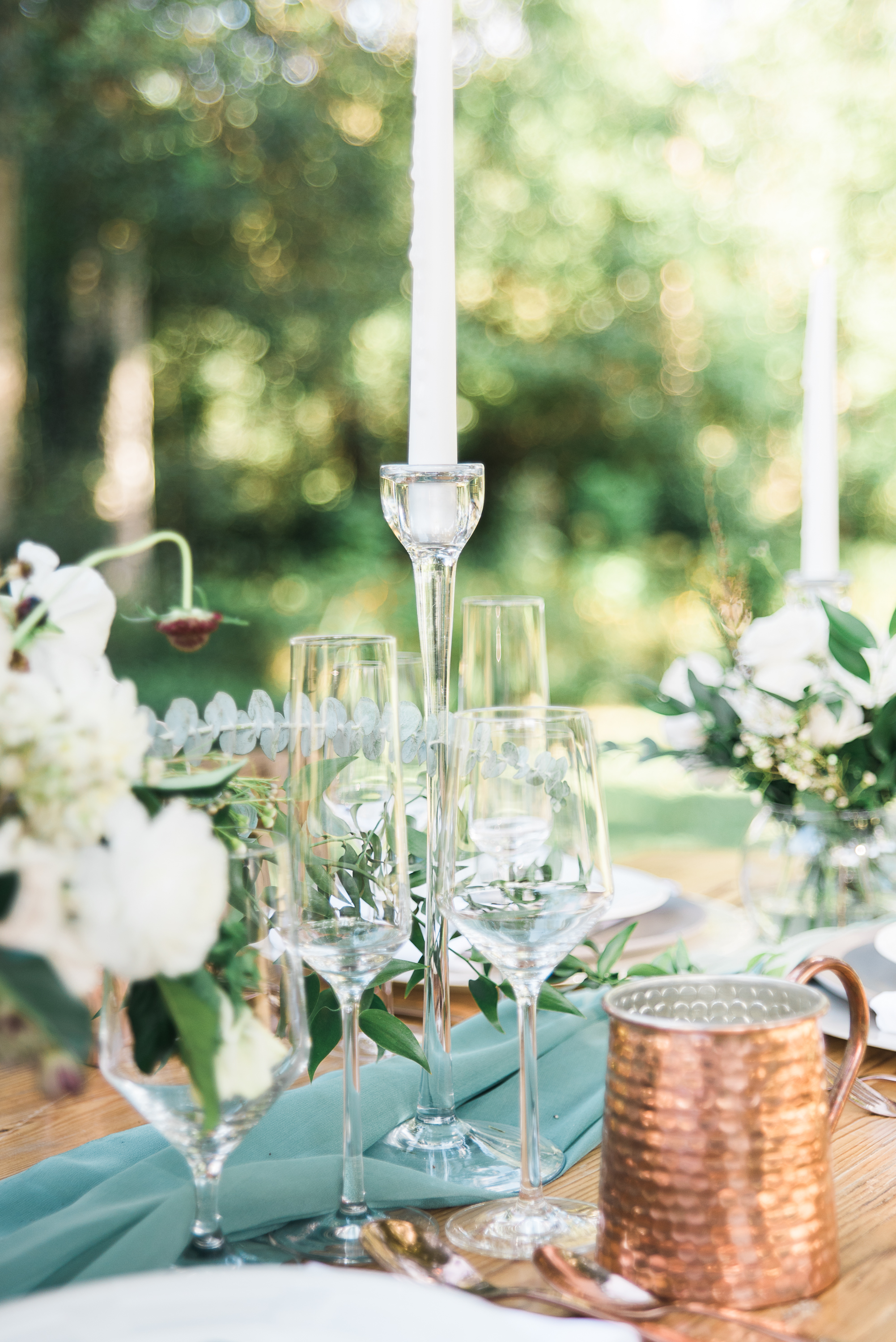 Gorgeous glassware for a wedding setup with a copper moscow mule mug.