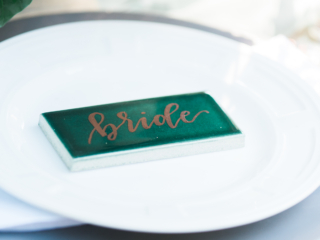 Calligraphy on green tile wedding place cards.