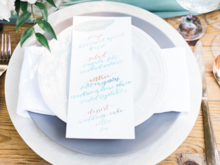 Calligraphy menu for a wedding with greenery inspired details.