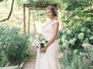 Gorgeous bride in a J Majors dress standing in the garden at The Ivy Place.