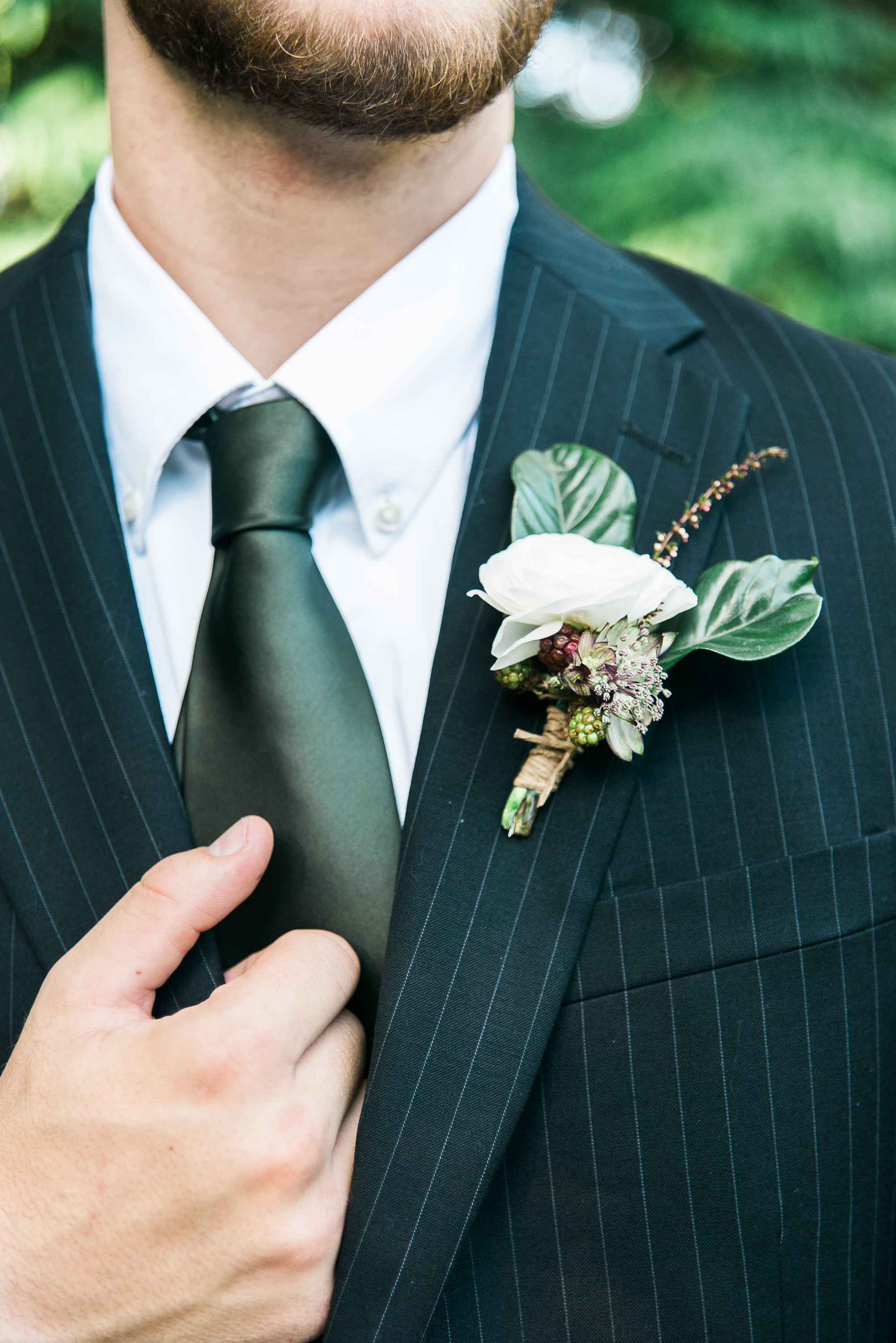 Groom's boutonniere with a dark green silk tie and black suit.