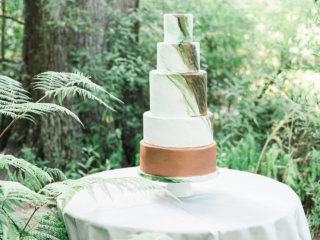 Marbled green wedding cake with copper accents.