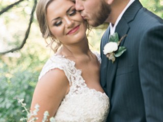 Bride and Groom kissing with makeup by Erin Ashley.