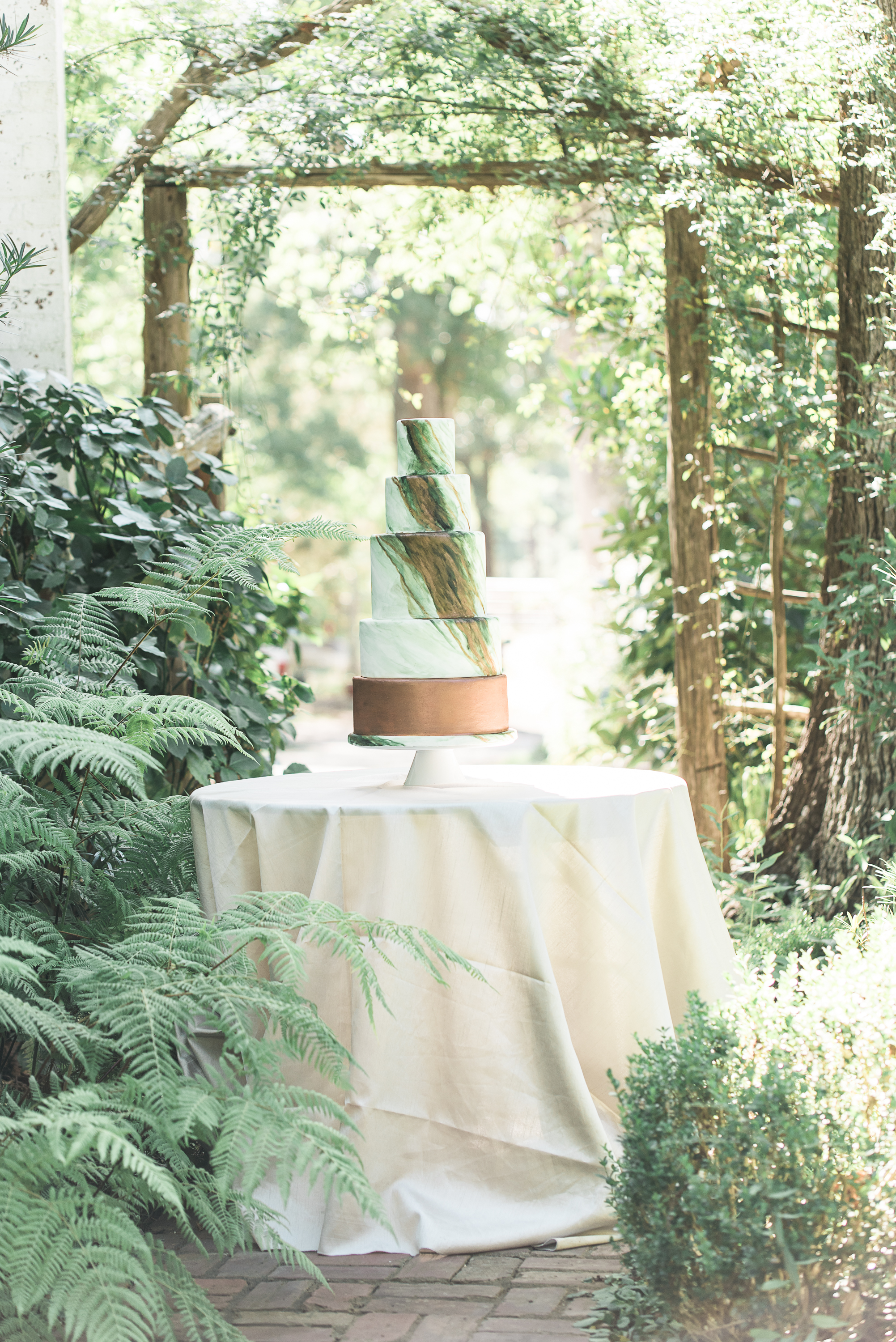 Gorgeous green marble wedding cake with copper accents.