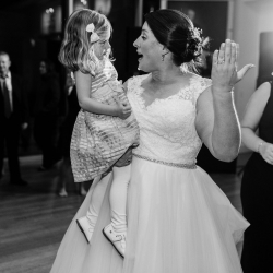 Bride dances with a young guest at her wedding coordinated and planned by Magnificent Moments Weddings