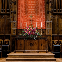 The alter of Myers Park United Methodist Church is decorated by Flower Diva with lush florals for a fall wedding