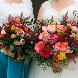 Bride and bridesmaids show off their stunning bouquets featuring bright pops of color created by Flower Diva