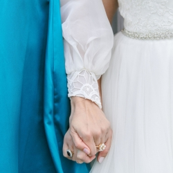 Bride holds hands with her maid of honor captured by Sunshower Photography for an Uptown Charlotte Wedding