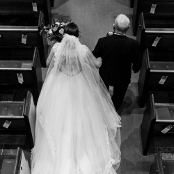 Sunshower Photography captures a bride and her father as they make their way down the aisle to her wedding ceremony in Uptown Charlotte, North Carolina