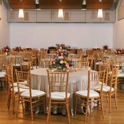 Gold Chiavari chairs, neutral linens, and pops of color in the centerpieces create a elegant atmosphere for a fall wedding at Foundation for the Carolinas