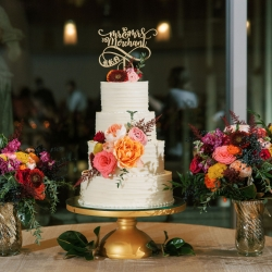 Four tiered white cake created by Edible Art Cake Shop feature a custom gold topper floral accents provided by Flower Diva