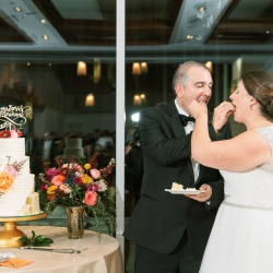 Bride and groom share some cake created by Edible Art Cake Shop during their fall wedding captured by Sunshower Photography