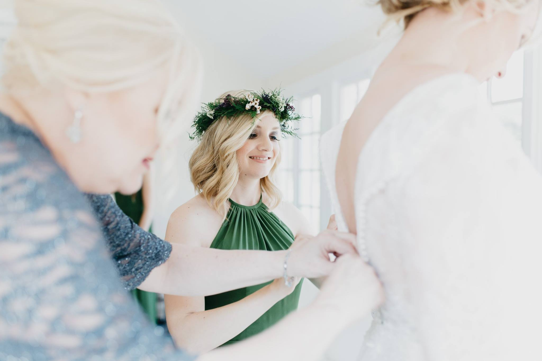 Bridesmaid in green dress with floral crown helping bride into her dress.