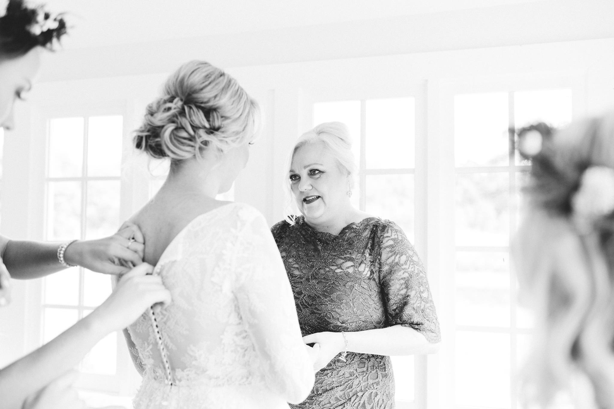 bride and her mother having a conversation while getting ready