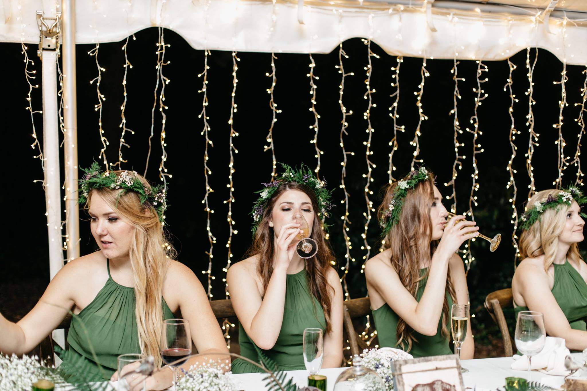 Bridesmaids in green Azazie dresses with floral crowns and twinkle lights