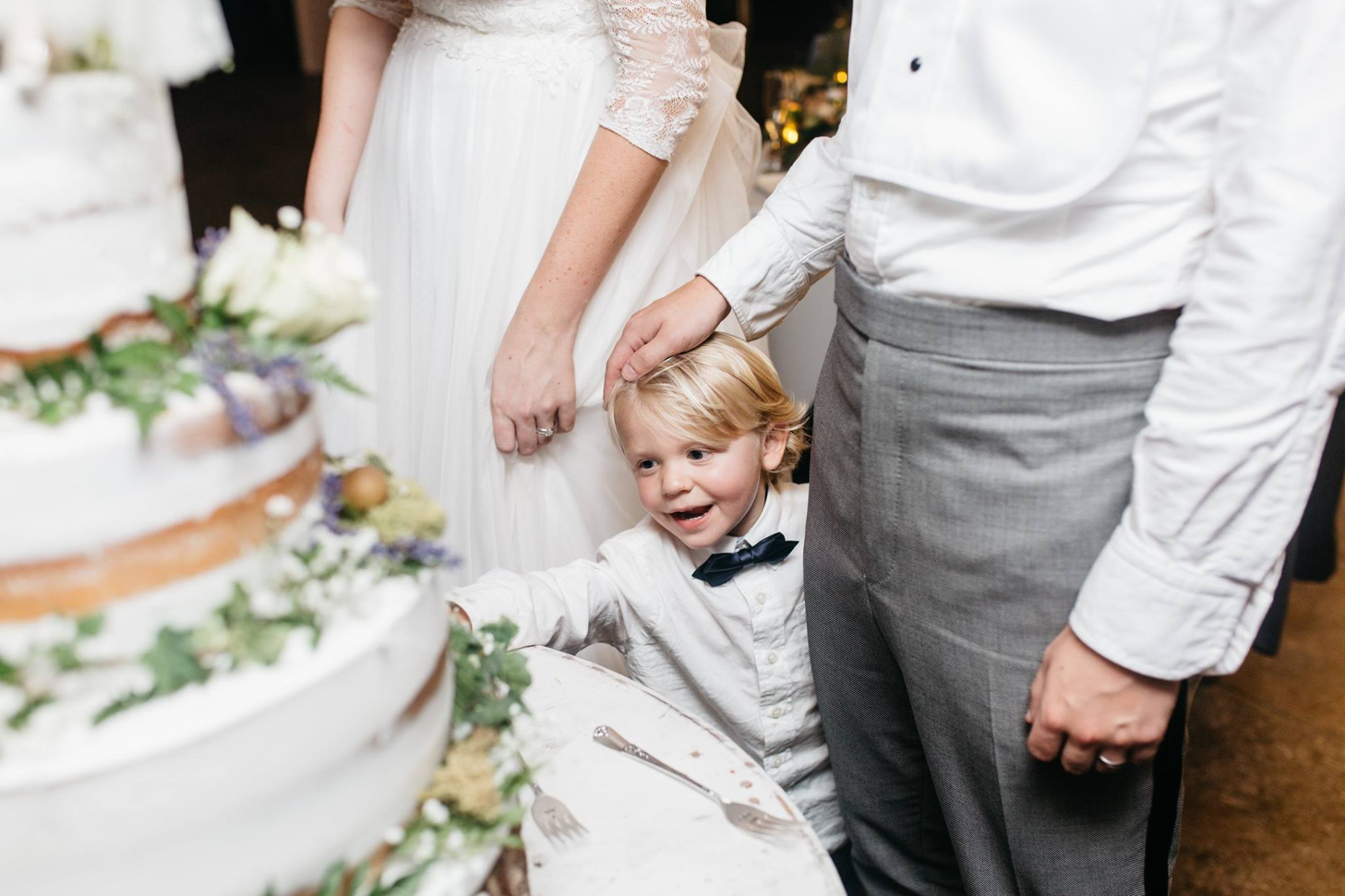 ring bearer reaching for the wedding cake