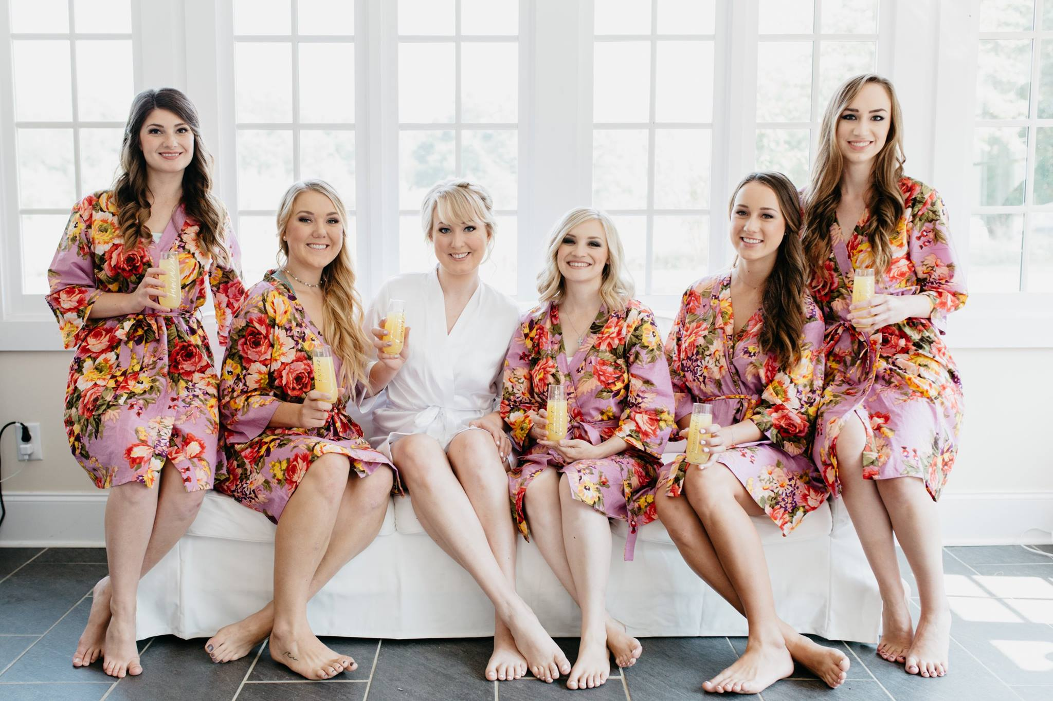 bride and bridesmaids getting ready in floral robes with mimosas