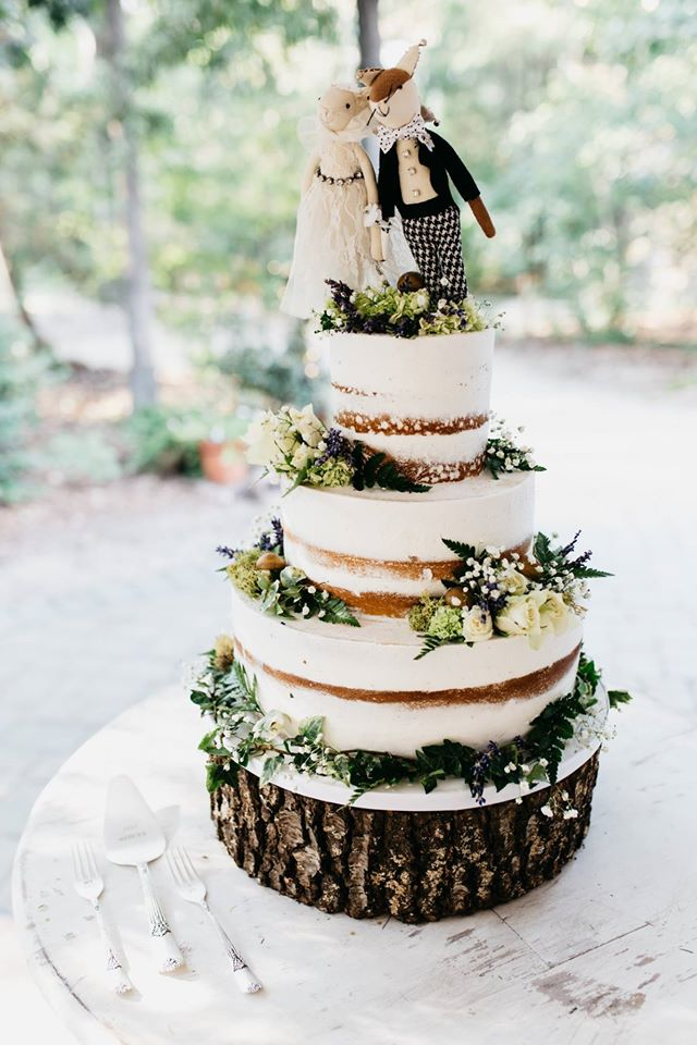 Woodland themed semi-naked wedding cake with greenery on a wood stand with cute fox toppers by Wow Factor Cakes.