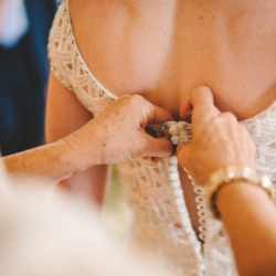Mother of the Bride buttoning her daughter's wedding dress
