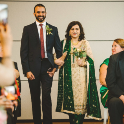 Groom walking his mother down the aisle