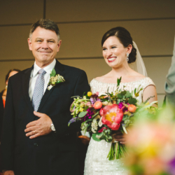 bride walking down the aisle escorted by her dad