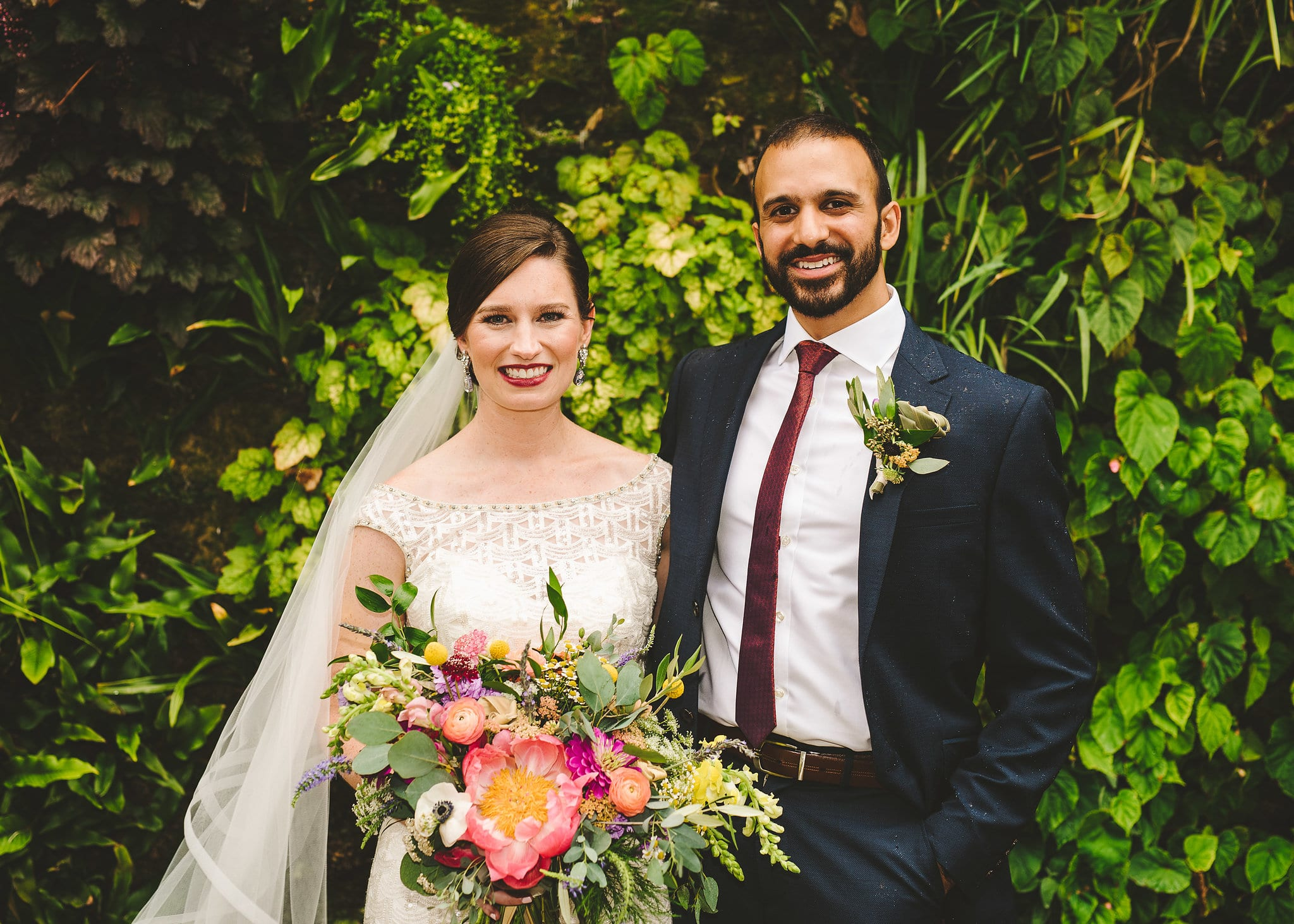 Wedding photos at the living wall at Foundation for the Carolinas in uptown Charlotte, NC with a gorgeous peony and colorful floral bouquet